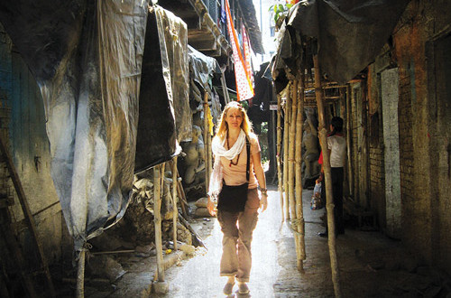 Woman walking down narrow alley - Seva India