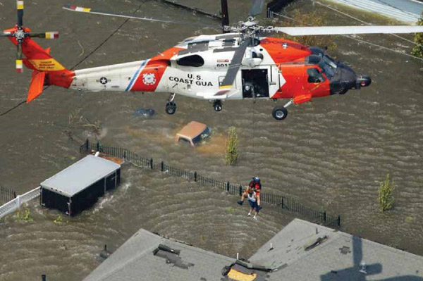 The crew of a Coast Guard MH-60 Jayhawk rescues an individual trapped on their rooftop by Hurricane Katrina. USCG Photo