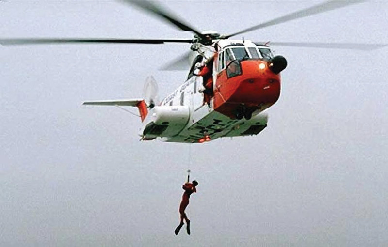 A Coast Guard HH-3F hoists a rescue swimmer from the sea. USCG photo